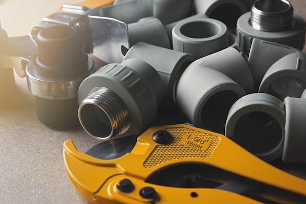 Closeup racores de plástico soldador y tijeras para tubos de pvc de polipropileno