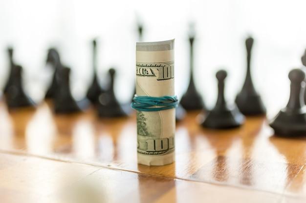 Closeup retorcido dólares americanos en tablero de ajedrez contra piezas negras