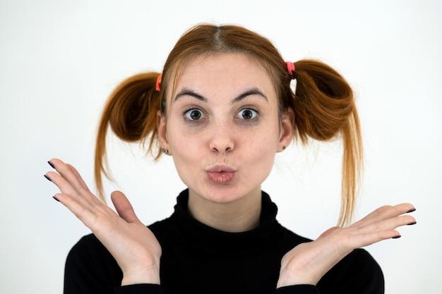 Closeup retrato de una adolescente pelirroja divertida con peinado infantil aislado