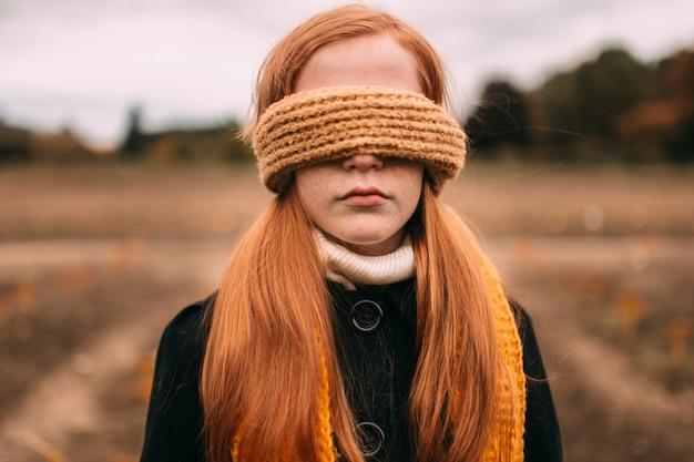 Closeup retrato al aire libre de niña pecas con los ojos vendados