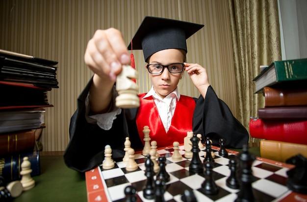Closeup retrato de chica inteligente en gorro de graduación haciendo movimiento en el ajedrez con caballo