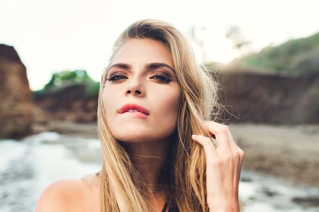 Closeup retrato de chica rubia sexy con cabello largo posando en la playa rocosa. se muerde los labios y mira a la cámara.
