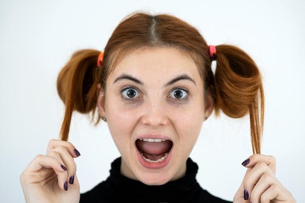 Closeup retrato de una divertida pelirroja adolescente con peinado infantil sonriendo felizmente aislado