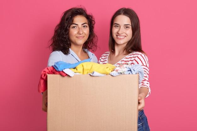 Closeup retrato de dos adorables mujeres con cabello oscuro, mirando a la cámara con una sonrisa