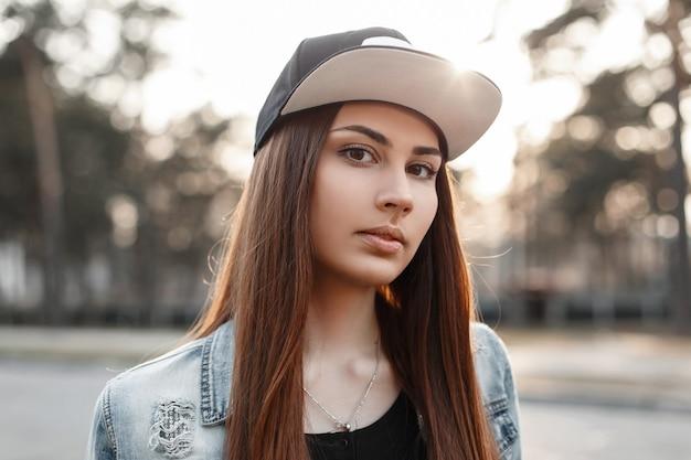 Closeup retrato de una hermosa chica hipster en una gorra de béisbol negra y chaqueta de jeans azul rasgada al atardecer
