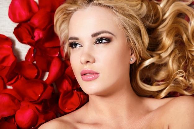 Closeup retrato de la hermosa chica rubia soñando con rosas rojas de pelo largo y rizado y maquillaje brillante