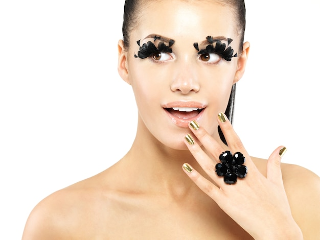 Closeup retrato de la hermosa mujer con maquillaje de pestañas postizas negras largas y uñas doradas. aislado en la pared blanca