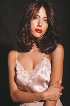Closeup retrato de hermosa mujer morena sensual. chica en ropa clásica beige elegante. modelo con labios rojos aislado en negro