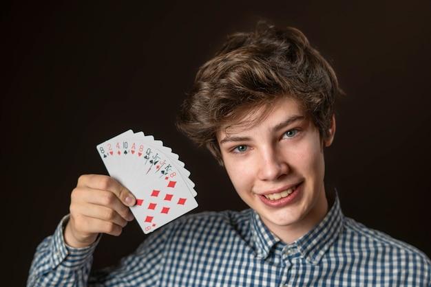 Closeup retrato de hombre adolescente mantenga la tarjeta de juego mostrarlo y cubrir la cara b