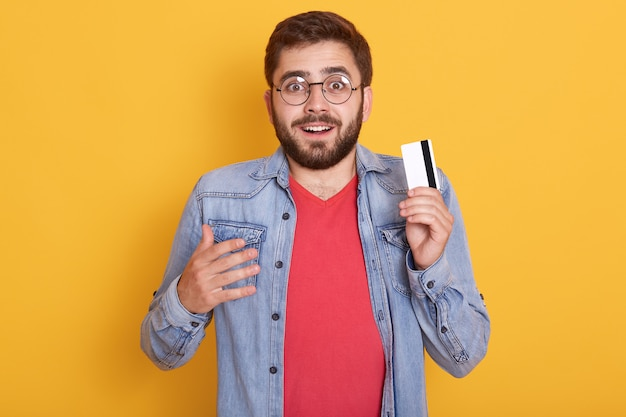 Closeup retrato de hombre barbudo asombrado con tarjeta de crédito en las manos, se ve emocionado, descubrió una gran cantidad de dinero en la tarjeta