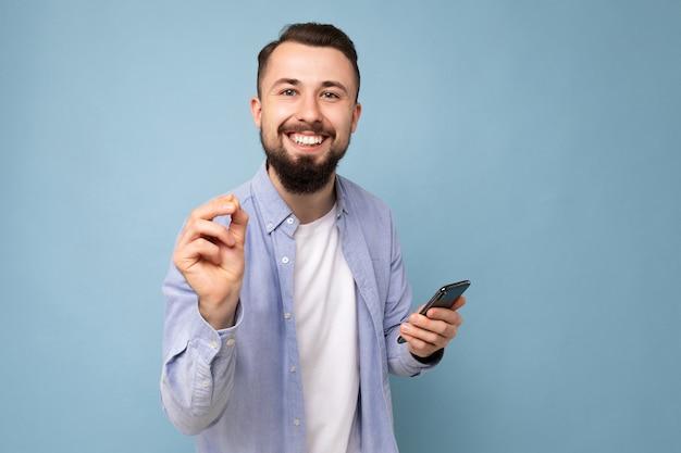 Closeup retrato de hombre barbudo brunet joven apuesto emocional positivo vistiendo azul casual