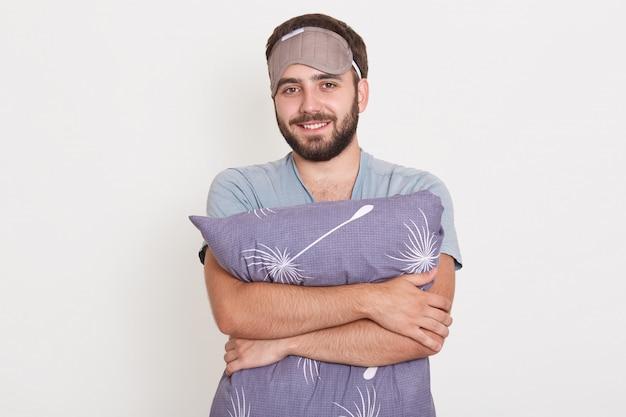 Closeup retrato de hombre barbudo sonriente abrazando una almohada gris, posando contra la pared blanca después de despertarse, usando una máscara para dormir
