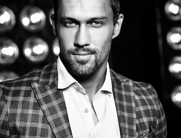 Closeup retrato de hombre modelo masculino de moda guapo sexy vestido con traje elegante sobre fondo negro de luces de estudio