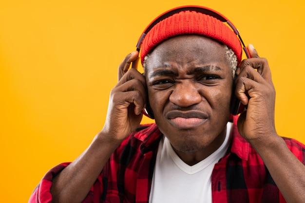 Closeup retrato de un hombre negro elegante avergonzado en auriculares rojos