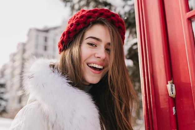 Closeup retrato increíble agradable joven con cabello largo morena, con sombrero rojo, expresando emociones positivas en la calle llena de nieve. tiempo de invierno frío, humor alegre.