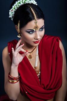 Closeup retrato de joven bella mujer en estilo indio, signo de dedo tradicional