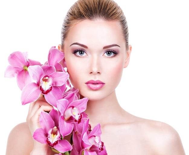Closeup retrato de joven bella mujer con una piel limpia y sana de la cara. chica bastante adulta con flor cerca de la cara. - aislado en fondo blanco
