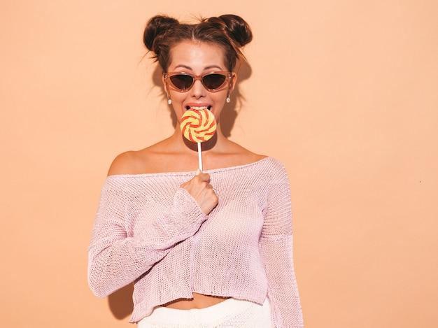 Closeup retrato de joven bella mujer sexy sonriente con peinado ghoul. chica de moda en ropa casual de verano en gafas de sol. modelo caliente aislado en beige. comer, morder paleta de caramelo
