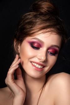 Closeup retrato de joven bella mujer sonriente con maquillaje de verano moderno de ojos ahumados rosa brillante