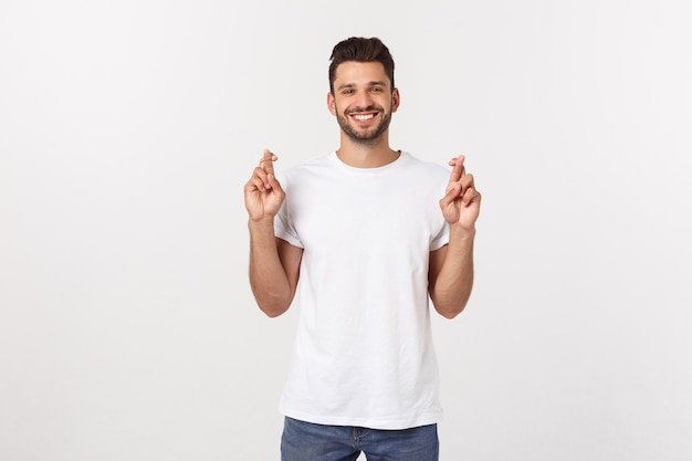 Closeup retrato de joven guapo cruzando los dedos, deseando, orando por milagro, esperando lo mejor, aislado en blanco.
