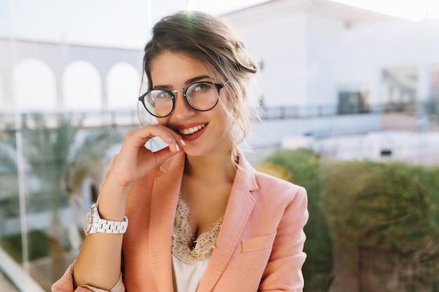 Closeup retrato de joven hermosa con gafas elegantes, bonita estudiante, mujer de negocios con elegante chaqueta rosa, blusa beige con encaje, maquillaje de día. ventana grande con vista al patio.