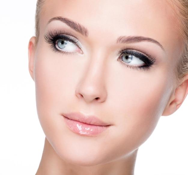 Closeup retrato de joven hermosa mujer blanca con largas pestañas postizas sobre pared blanca