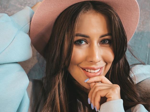 Closeup retrato de joven hermosa mujer sonriente mirando. chica de moda en ropa casual de verano con capucha y falda.