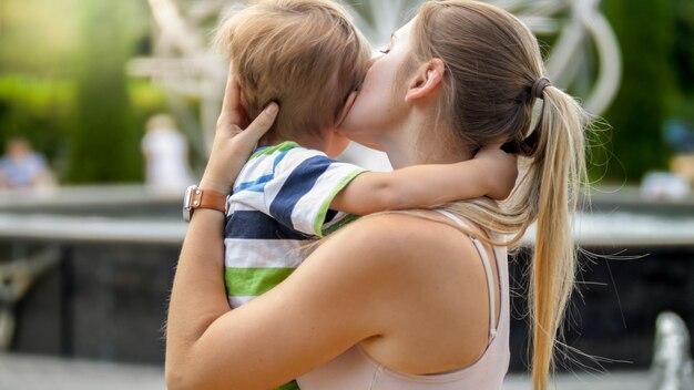 Closeup retrato de joven madre abrazando y acariciando a su niño pequeño llorando en el parque