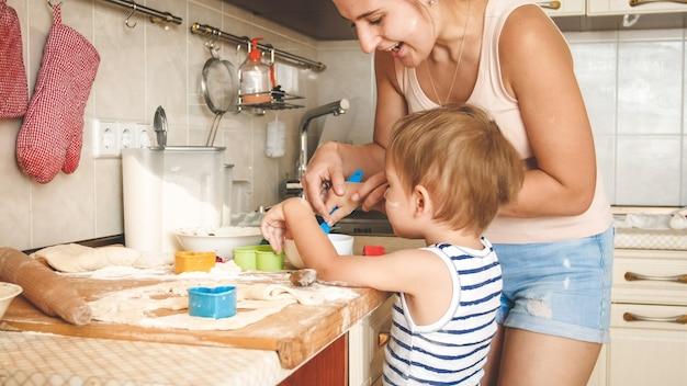 Closeup retrato de joven madre con niño pequeño sosteniendo una bandeja para hornear y haciendo galletas en la cocina