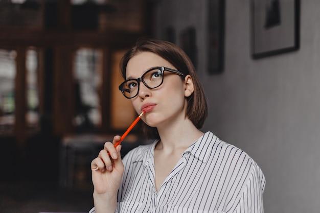 Closeup retrato de joven mujer de negocios de pelo corto con gafas mirando pensativamente y sosteniendo un lápiz rojo.