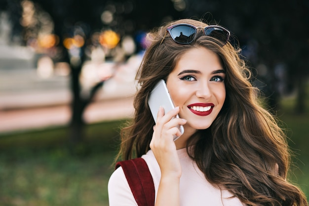 Closeup retrato de linda chica con maquillaje efectivo y cabello largo hablando por teléfono en el parque. tiene labios vinosos y sonrientes.
