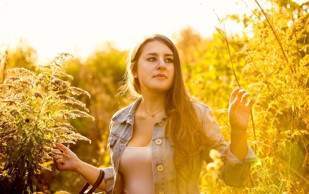 Closeup retrato de linda mujer morena caminando en la pradera llena de luz solar