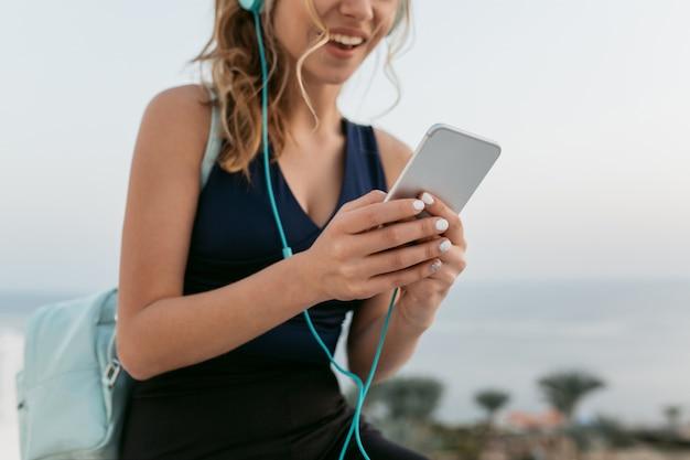 Closeup retrato de manos de mujer joven y bonita en ropa deportiva charlando por teléfono. disfrutar frente al mar, escuchar música a través de auriculares, divertirse, sonreír