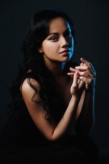 Closeup retrato de moda de la hermosa modelo elegante mujer joven de raza blanca con retroiluminación azul.