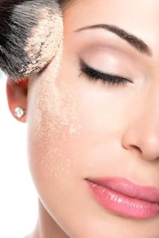 Closeup retrato de una mujer aplicando base tonal cosmética seca en la cara con pincel de maquillaje.