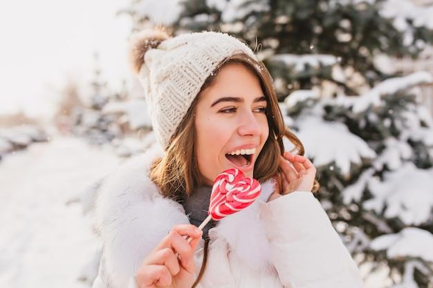 Closeup retrato mujer divertida linda con sombrero de lana blanco divirtiéndose con lollypop de corazón rosa en la calle. bastante joven disfrutando del frío invierno, nieve, emociones brillantes.