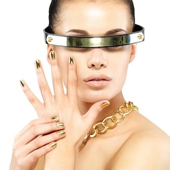 Closeup retrato de mujer con uñas doradas y cadena de oro en el cuello