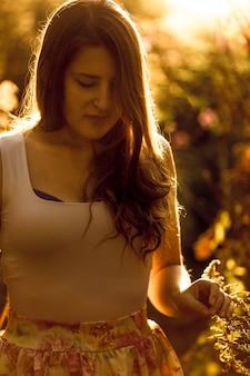 Closeup retrato de mujer joven elegante caminando en el campo al atardecer