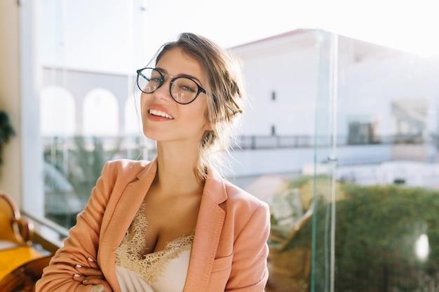 Closeup retrato de mujer joven con gafas elegantes, elegante dama en elegante chaqueta rosa con blusa beige, linda estudiante. ventana grande con linda vista.