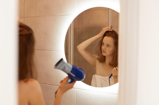Closeup retrato de una mujer joven infeliz mirando su cabello dañado, sosteniendo secador de pelo, mirando su reflejo en el espejo con expresión facial triste.