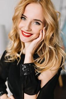 Closeup retrato de mujer joven sonriente con cabello ondulado rubio largo. vistiendo elegante blusa negra, vestido con lentejuelas, maquillaje de día ligero con lápiz labial rojo.