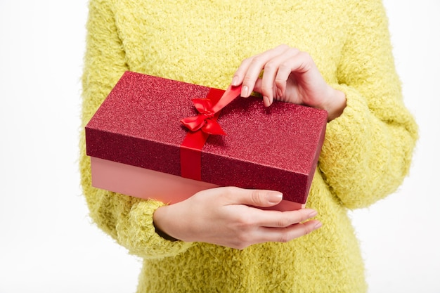 Closeup retrato de una mujer manos sosteniendo caja de regalo