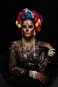 Closeup retrato de una mujer con un maquillaje de calavera de azúcar vestida con corona de flores