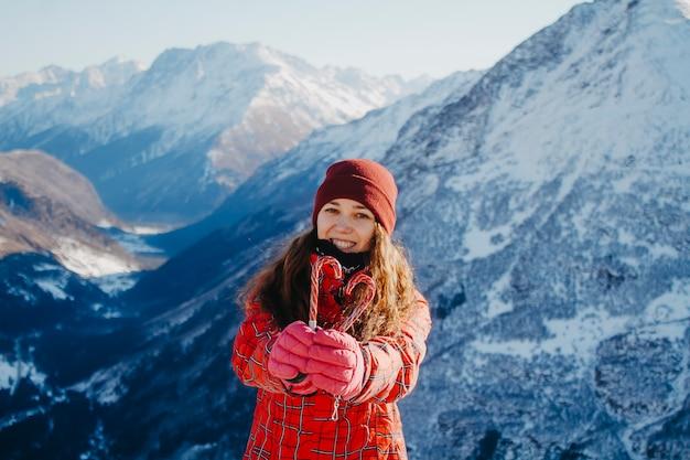 Closeup retrato de mujer en las montañas con un corazón en sus manos.