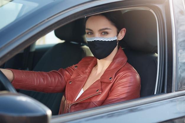 Closeup retrato de mujer morena conduciendo coche, mujer con chaqueta de cuero y máscara protectora negra, la señora va a la tienda de comestibles comprando comida de conveniencia