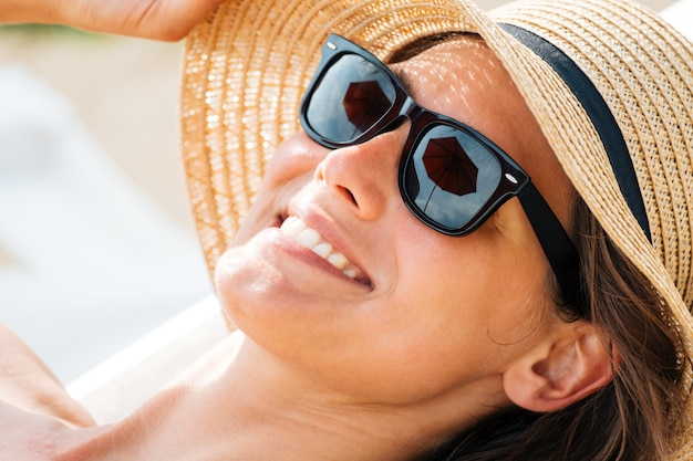 Closeup retrato de una mujer oculta su rostro del sol bajo un sombrero de paja