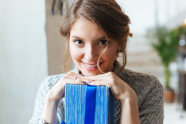 Closeup retrato de una mujer sonriente con caja de regalo mirando a la cámara