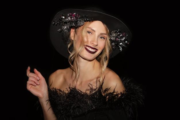 Closeup retrato de niña bonita en vestido negro con boa y sombrero de ala ancha con flores sobre fondo negro