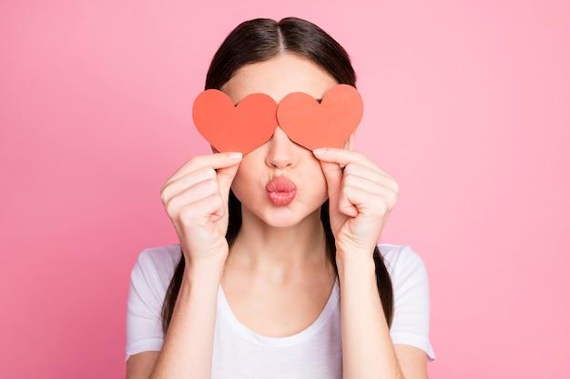 Closeup retrato de niña coqueta cerrando los ojos con corazón rojo enviando beso de aire