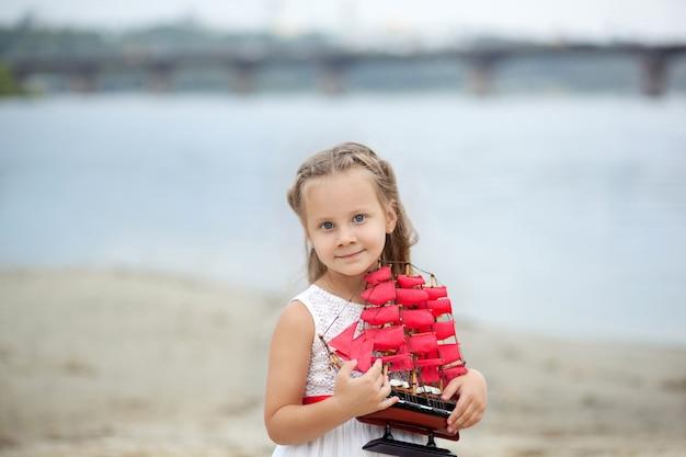 Closeup retrato de niña feliz en manos sostiene un velero de juguete con velas escarlatas. niña con el pelo rubio en el vestido blanco que sostiene la nave.